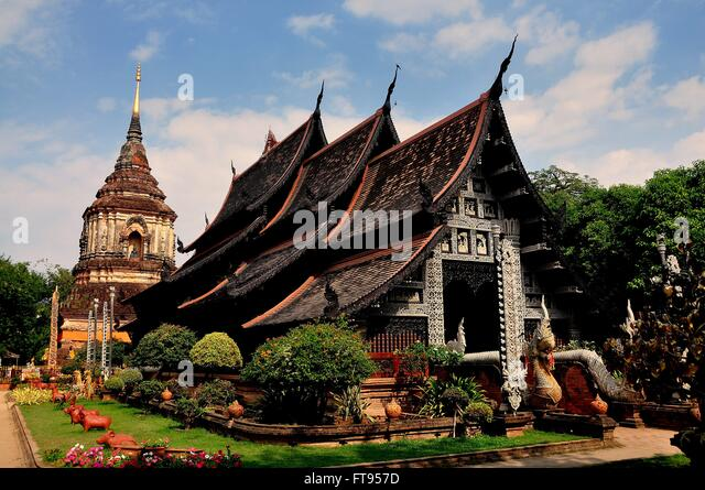 Chiang Mai,Thailand:  Lanna style teakwood Vihan hall with it carved facade and the great brick chedi - Stock-Bilder