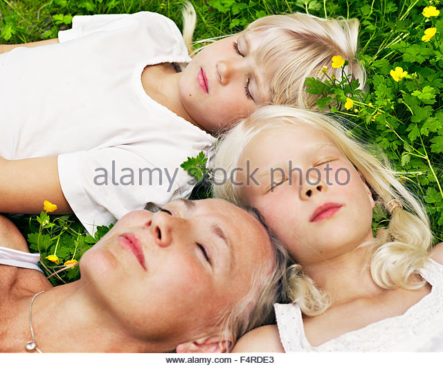 Mother with two daughters (8-9) relaxing in local park - Stock Image