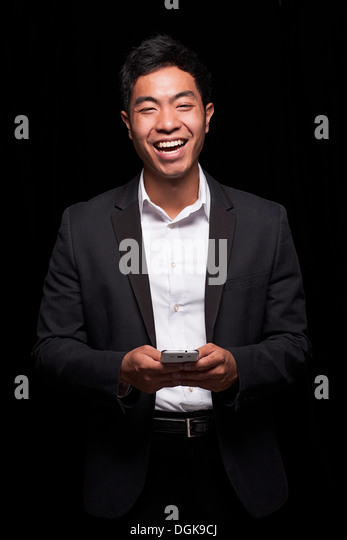 Businessman using smartphone, laughing - Stock Image