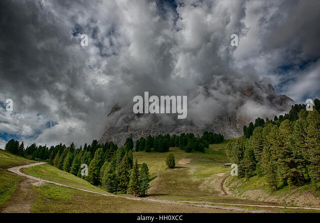 Storm clouds over the top of the mountains in a summer season, Dolomites - Stock Image