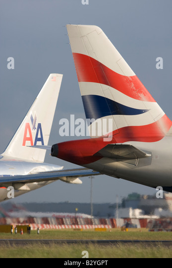 The tails of British Airways and American Airlines planes - London Heathrow, United Kingdom - Stock Image