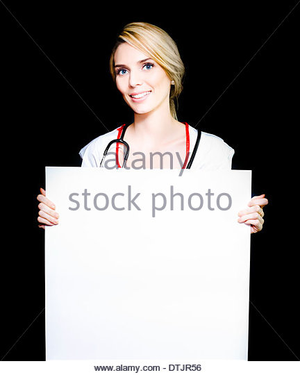 Beautiful female doctor holding blank board on black background - Stock Image
