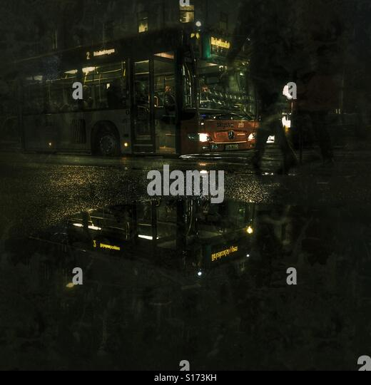 Buss reflected in puddle - Stock Image