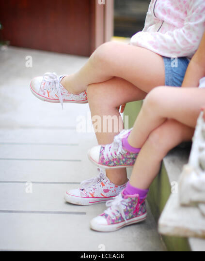 Argentina, Buenos Aires, Sisters sitting cross-legged side by side - Stock Image