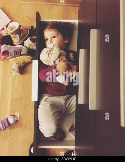 Cute little girl lying in shoe closet shelf top view - Stock-Bilder