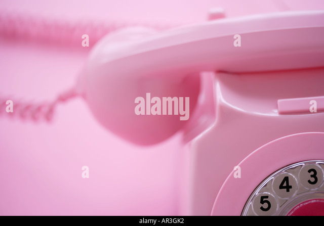 Detail of a pink telephone receiver on pink background - Stock Image