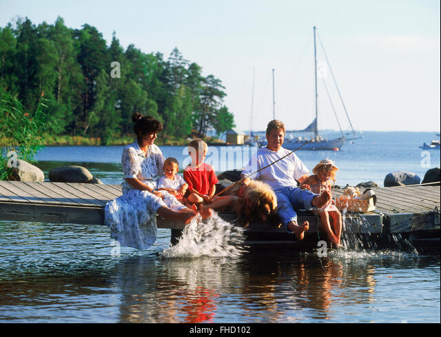Dad and Mom with three kids and family dog sitting on lakeside pier during fishing picnic in Sweden - Stock Image