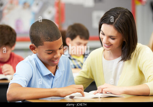Teacher Reading With Male Pupil In Class - Stock Image