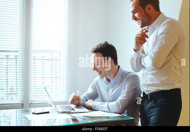 two young business men laughing in front of computer - Stock Image