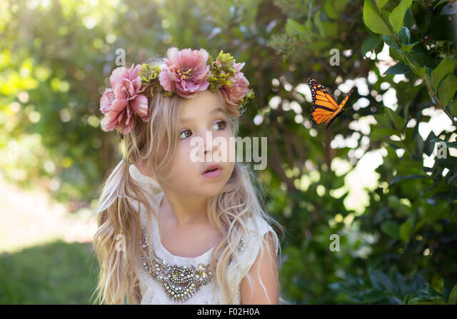 Girl watching a butterfly - Stock Image