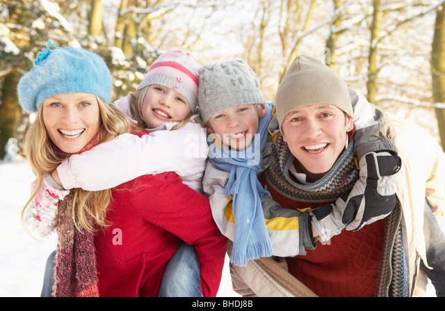Family Having Fun Snowy Woodland - Stock Image