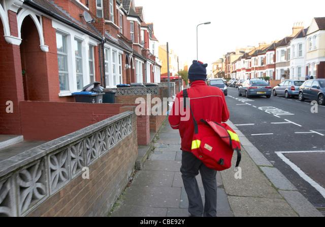 postman delivering mail on a cold december morning in cricklewood north london england united kingdom uk - Stock Image