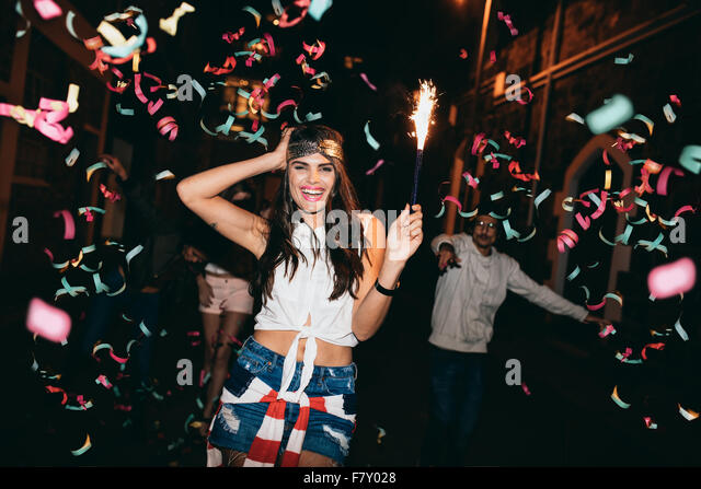 Happy young woman partying with her friends outdoors at night. Friends partying outdoors with confetti and sparklers. - Stock Image