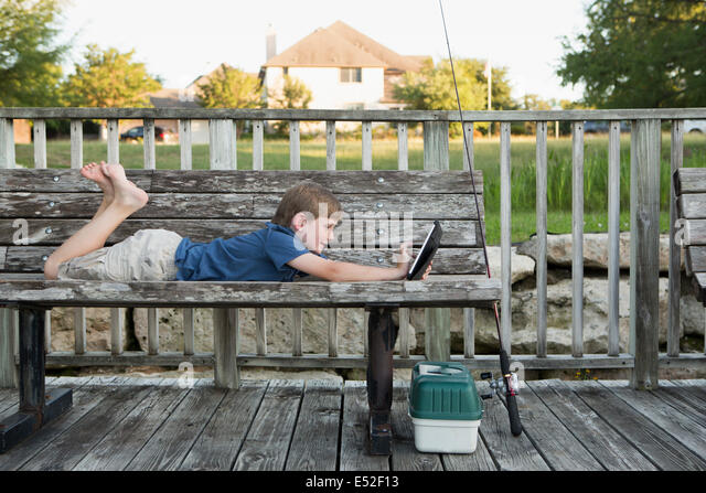 A young boy outdoors lying on a bench using a digital tablet. fishing equipment. - Stock Image