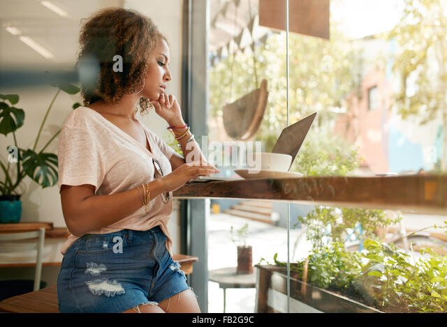 Shot of a young woman using her laptop in a coffee shop. African female sitting in cafe surfing internet on her - Stock Image