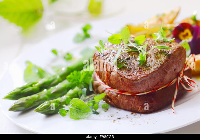 Medallion of roast fillet steak tied with string and served with fresh green asparagus tips and spears liberally - Stock Image
