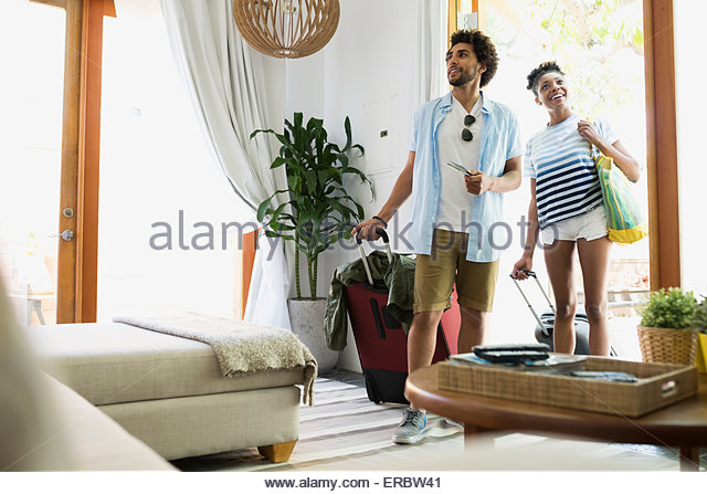 Couple with suitcases arriving at vacation house - Stock-Bilder