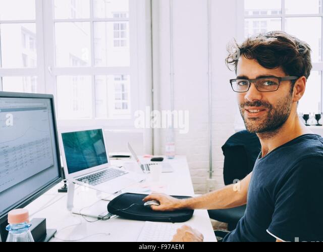 Portrait Of A Man Working On Computer In Office - Stock-Bilder