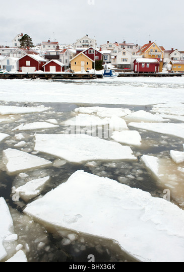 View of traditional village of Grundsund during winter with sea ice n Bohuslan coast in Sweden - Stock Image