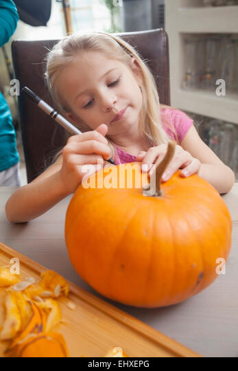 Girl carving pumpkin for Halloween, Bavaria, Germany - Stock Image
