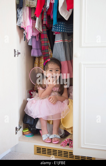 Girl in princess costume hiding in cupboard - Stock Image