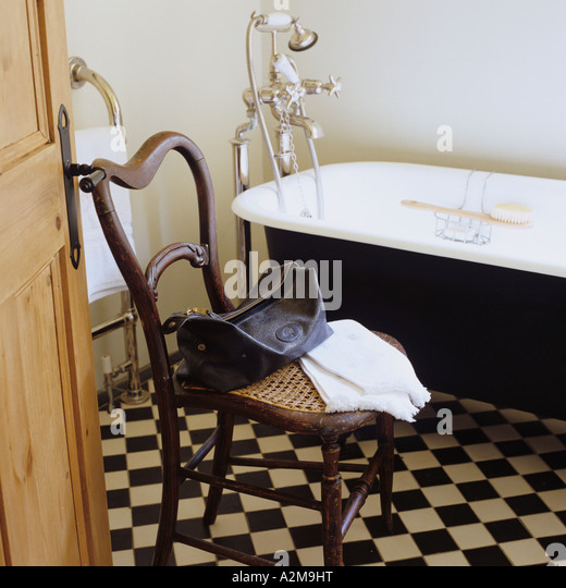 Washbag and towel on chair in bathroom with checkered floor tiles - Stock-Bilder