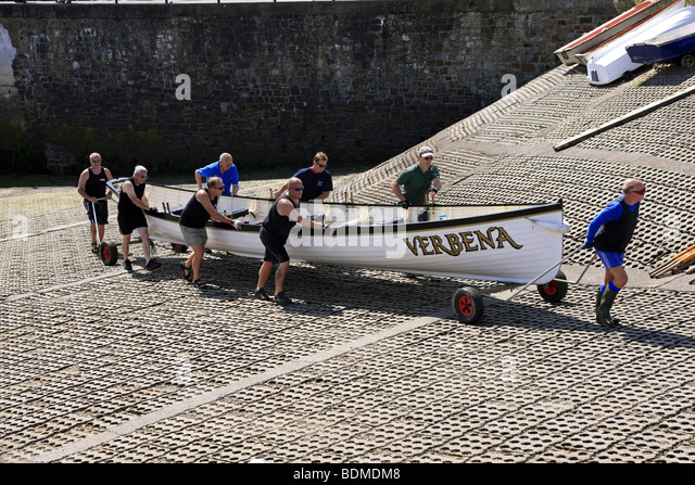Crewmen of the Gig rowing boat called the Verbena wheel the boat up the jetty at Appledore Devon England - Stock Image