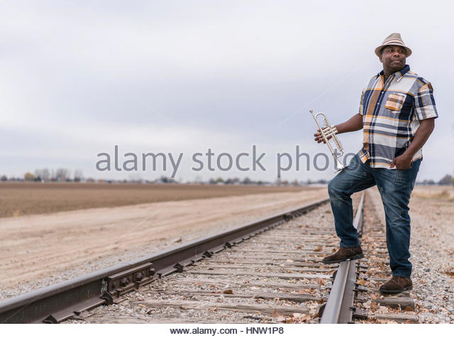 Curious Black man standing on train track holding trumpet - Stock-Bilder