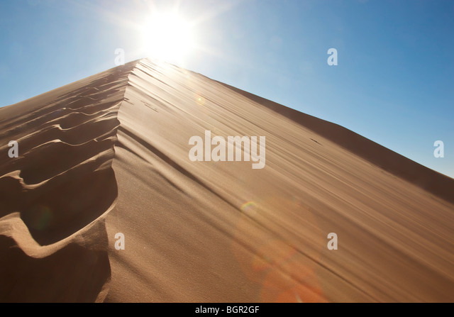 footprints on sand dune with sun and blue sky - Stock Image
