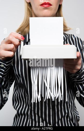 Woman shredding paper - Stock Image