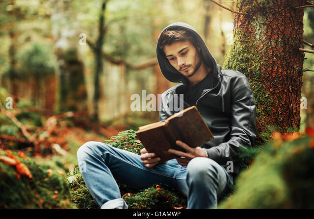 Man reading in nature and relaxing outdoors, freedom and individuality concept - Stock Image