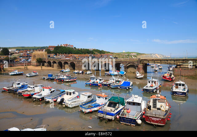 Working fishing boats beached at low tide in Folkestone Harbour. - Stock Image