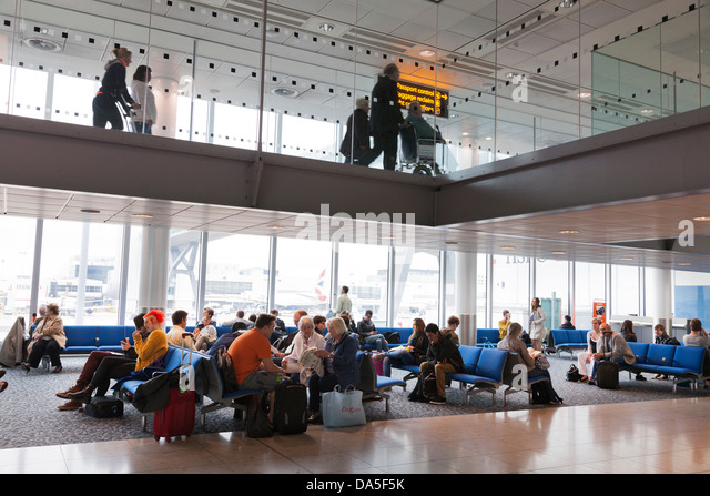 passengers waiting in airport departure lounge below arrivals corridor - Stock-Bilder