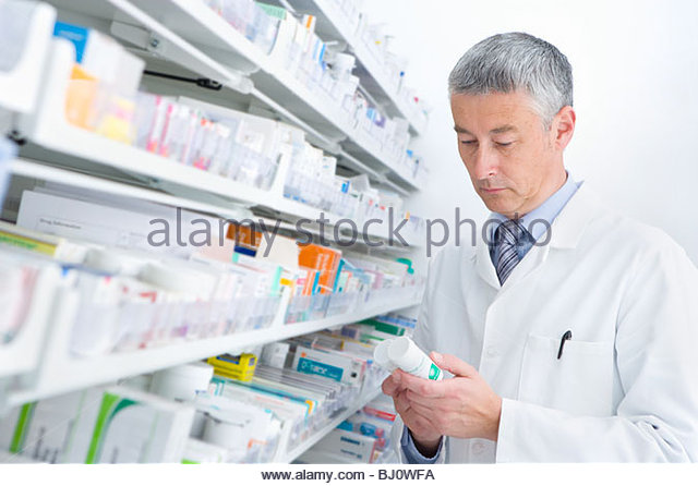 Pharmacist reading medicine bottle in pharmacy - Stock Image