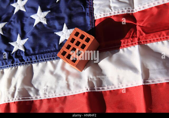 single brick lyinon the Stars and Stripes flag of America: Symbol for Donald Trumps wall to be built aat the boarder - Stock Image