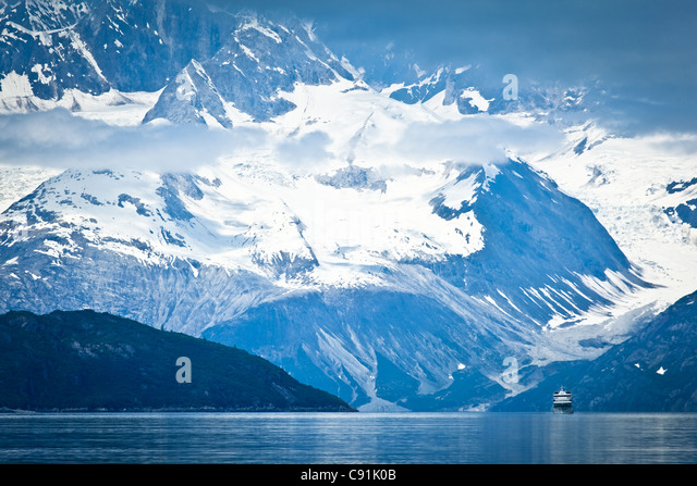 A small cruise ship sailing through Tarr Inlet with the Fairweather Range in the background, Glacier Bay National - Stock Image