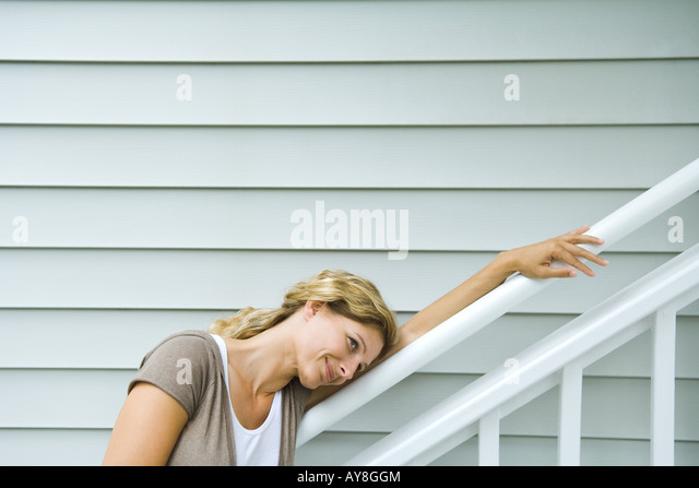 Woman leaning head against railing, smiling, looking away - Stock Image