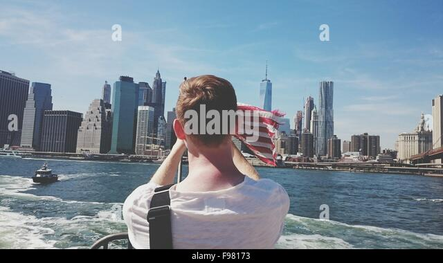 Rear View Of Man On Ferry Boat Against City - Stock Image