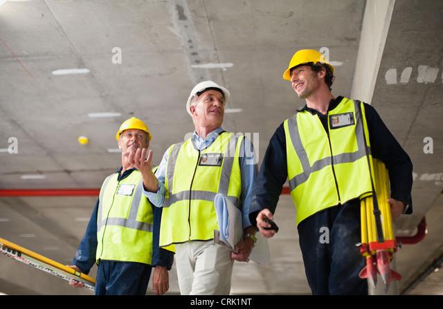 Workers walking at construction site - Stock-Bilder