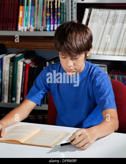 Teenage Schoolboy Reading Book In Library - Stock Image