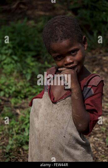 Shy boy watches the foreigners in the forest. - Stock Image