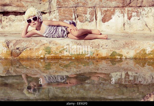 Girl lounging beside rock pool - Stock-Bilder