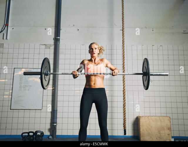 Young strong woman practices cross fit in a gym. Fit female holding a barbell with weights for crossfit. - Stock-Bilder