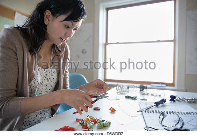 Beautiful woman cutting wire while making jewelry at desk - Stock Image