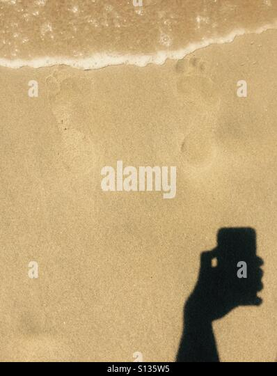 A shadow of an hand holding a phone taking a photo of some footprints in the sand. - Stock Image