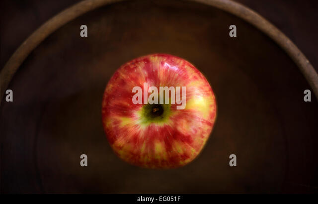 An apple in a rustic wooden bowl. - Stock Image