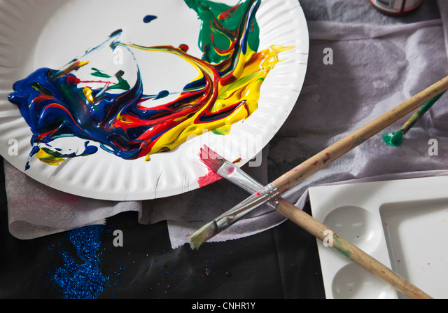 Heaps of acrylic paint on a paper plate and paintbrushes - Stock Image