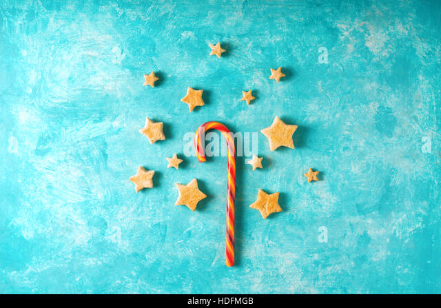 Christmas candy and cookies on the blue background top view - Stock Image