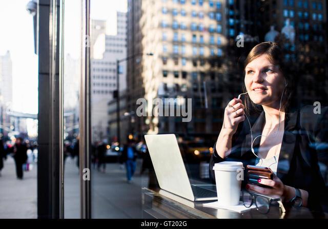 Businesswoman with headphones using laptop at coffee shop seen through window - Stock-Bilder
