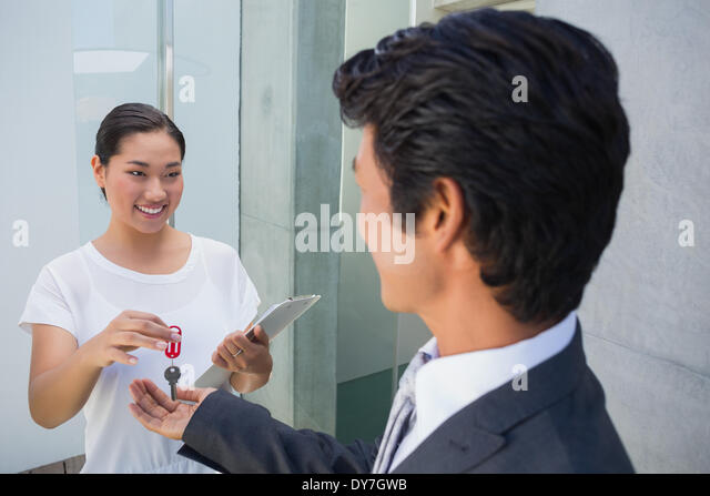 Estate agent giving house key to buyer - Stock Image